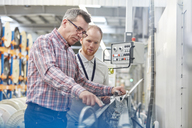 Male supervisor and worker examining machinery in fiber optics factory - CAIF07190