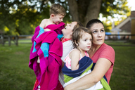Lesbian mothers holding wet children wrapped in a towel in summer yard - CAIF07232