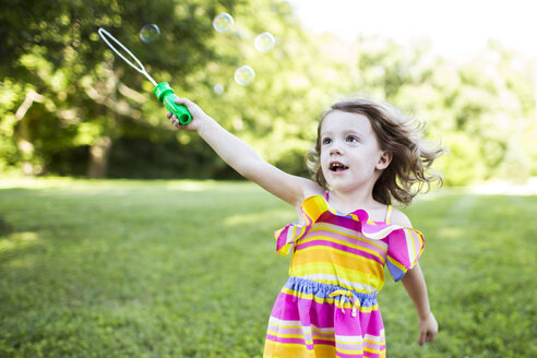 Preschool girl playing with bubble wand in summer yard - CAIF07235