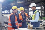 Male engineers discussing steel part in factory - CAIF07259