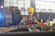 Male worker with tape measure measuring steel in factory - CAIF07265