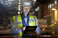 Male engineer working at glowing digital tablet in dark factory - CAIF07268