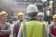 Male foreman talking, meeting with workers in factory - CAIF07277