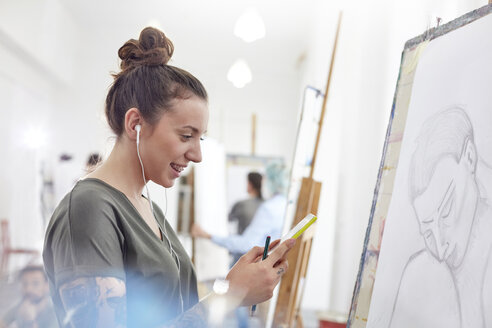 Smiling female artist with headphones listening to music and sketching in art class studio - CAIF07322