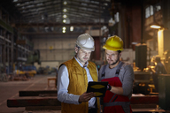 Male foreman and engineer using digital tablet in dark factory - CAIF07337