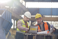 Male foreman and engineer working at laptop with blueprints in factory - CAIF07340