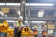 Male foreman with clipboard standing near workers in factory - CAIF07343