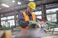 Male worker assembling steel part in factory - CAIF07355