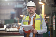 Portrait confident male foreman with clipboard in factory - CAIF07361