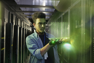 Male IT technician holding glowing futuristic digital tablet in server room - CAIF07364