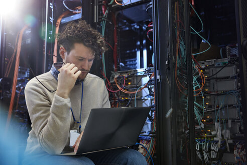 Focused male IT technician using laptop in server room - CAIF07394
