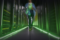 IT technician walking in dark, glowing server room - CAIF07400