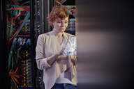 Female IT technician using futuristic digital tablet in server room - CAIF07406