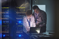 IT technicians working at laptop in dark server room - CAIF07409