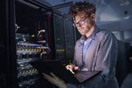 Focused male IT technician working at laptop in dark server room - CAIF07424
