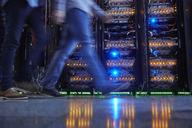 IT technicians walking in dark server room - CAIF07427