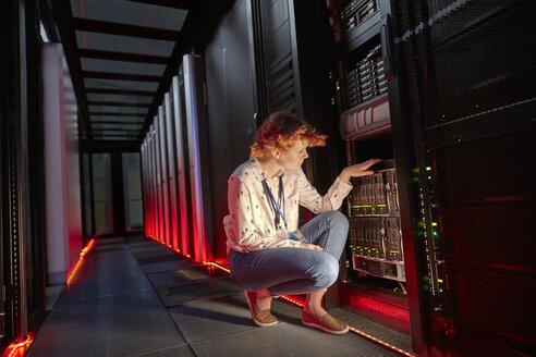 Female IT technician examining panel in dark server room - CAIF07433
