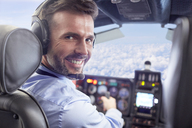 Portrait smiling, confident male pilot flying airplane in cockpit - CAIF07448