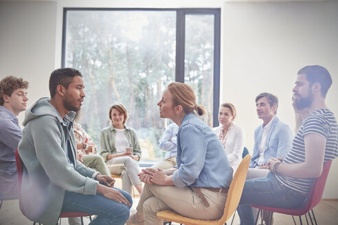 Group watching man and woman talking face to face in group therapy session - CAIF07484