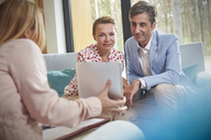 Therapist showing digital tablet to couple in couples therapy counseling session - CAIF07490