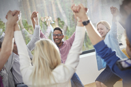 People smiling and holding hands in circle in group therapy session - CAIF07505