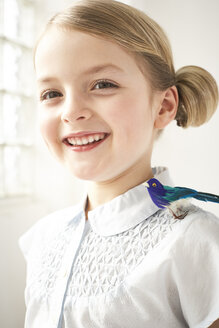 Portrait of happy little girl with toy bird on shoulder - FSF00997