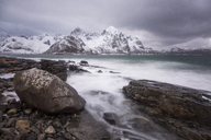 Snow covered mountains behind craggy cold lake, Haukland Lofoten Islands, Norway - CAIF07515