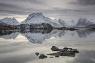 Reflection of snow covered mountain range in calm lake, Norway - CAIF07518