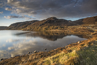 Sunny tranquil view of hills and bay, Scotland - CAIF07521
