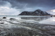 Snow covered rock formation on cold ocean beach, Skagsanden Beach, Lofoten Islands, Norway - CAIF07527