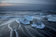 Long exposure of ice on cold stormy ocean beach, Jokulsarlon, Iceland - CAIF07539