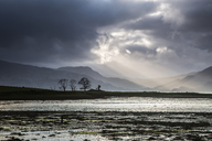 Sunbeams in stormy sky over lake, Scotland - CAIF07542