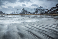 Snow covered mountains behind cold beach, Skagsanden Beach, Lofoten Islands, Norway - CAIF07545