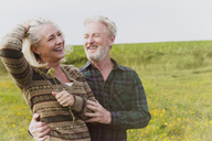 Smiling senior couple hugging in field - CAIF07554