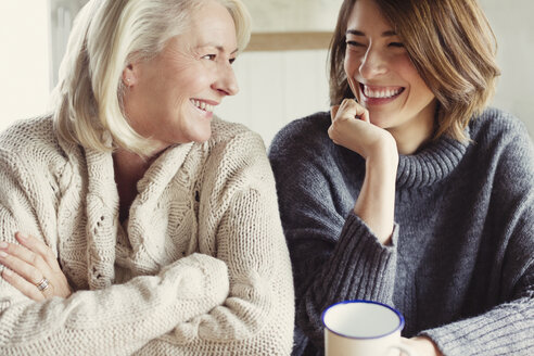 Laughing mother and daughter in sweaters drinking coffee - CAIF07557