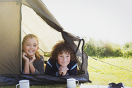 Portrait smiling brother and sister in tent - CAIF07563