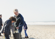 Multi-generation family clam digging on sunny beach - CAIF07566