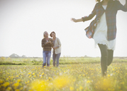 Women watching girl run in sunny meadow with wildflowers - CAIF07569