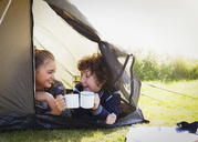 Brother and sister toasting mugs in tent - CAIF07572