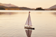 Toy sailboat in tranquil lake at sunrise, Lake District, Cumbria, England - CAIF07581