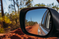 Red clay dust cloud in side-view mirror of car - CAIF07614