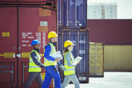 Business people and worker walking near cargo containers - CAIF07653
