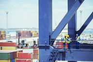 Business people and worker talking on cargo crane - CAIF07656