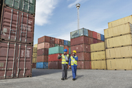 Worker and businessman talking near cargo containers - CAIF07662