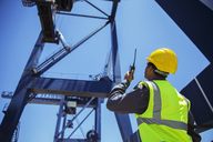 Low angle view of businessman using walkie-talkie under cargo crane - CAIF07665