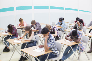 Students writing their GCSE examination in classroom - CAIF07689