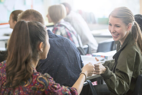 Smiling female students exchanging notes in classroom - CAIF07692
