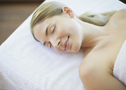 Serene woman laying on massage table - CAIF07719