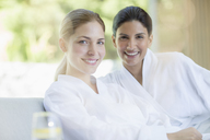 Portrait of smiling women in bathrobes at spa - CAIF07725