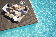 Couple laying on lounge chair at poolside - CAIF07731